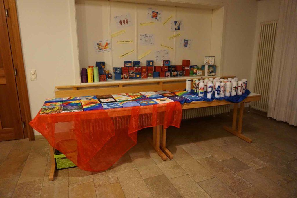 Ein Tisch voller gebastelter Konfirmations-Kerzen und gemalten Bildern